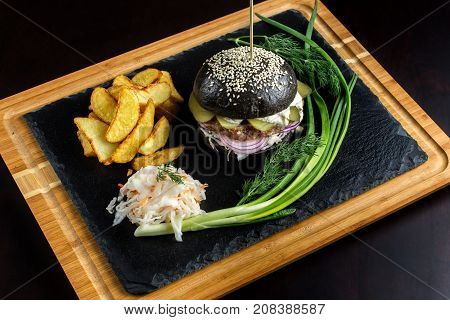 Black hamburger on stone table with black background. Fastfood meal. Delicious Hamburger. Top view.