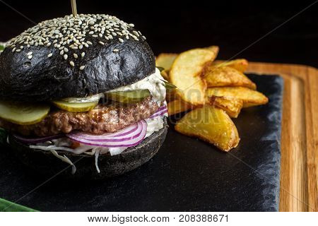French fries in the background hamburger. It is laid out on a black slate. Close Up.