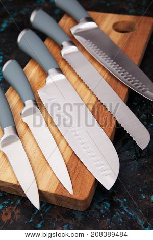 Set of five modern kitchen knives on wooden chopping board