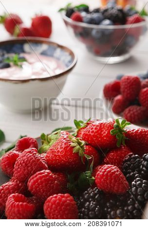 Tasty breakfast with light greek yogurt, fresh strawberries, raspberries, blueberries and blackberries. Low fat morning meals and healthy start of the day. Detox and diet concept, selective focus