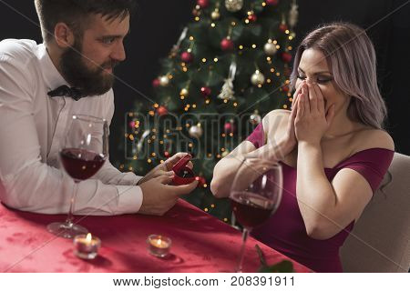 Young attractive couple in love sitting at a dinner table next to a nicely decorated Christmas tree while man surprises his girlfriend with an engagement ring