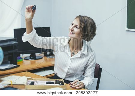 Teacher Happy Young Woman In The Class With Case Studies Of Minerals At The Work Place At The Table