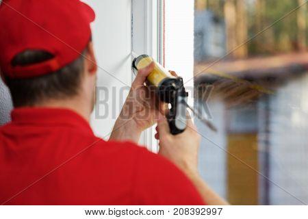 worker applying caulk around pvc window frame