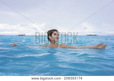 Gorgeous girl in a white swimsuit relaxing in the geothermal pool on the background of snow mountains and cloudy sky outdoors in Iceland. She looks to the side with a smile and outstretched arms.