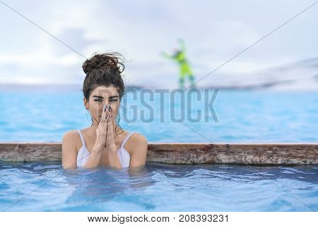 Delightful girl in a white swimsuit relaxing in the geothermal pool on the background of snow mountains and cloudy sky outdoors in Iceland. She looks into the camera and holds her palms together.