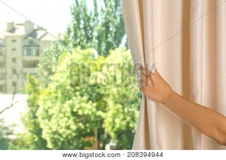 Woman holding modern curtains in room