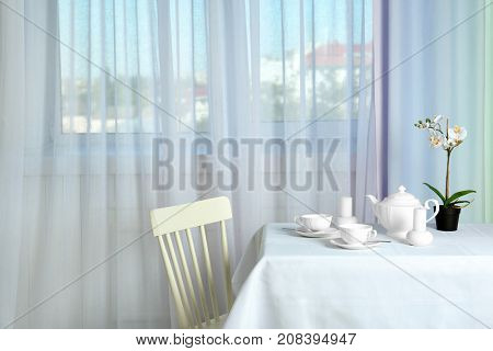 Serving table near window with modern curtains in room