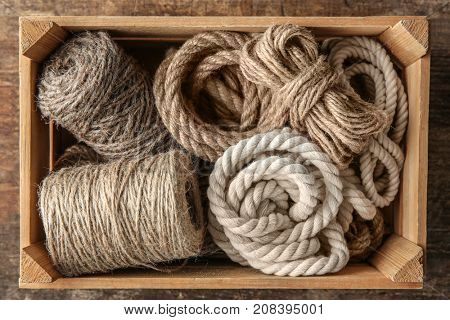 Hemp ropes in crate on wooden background