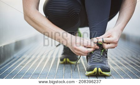 Sports in a city - woman tying her jogging shoe. Shallow DOF focus on the shoe.