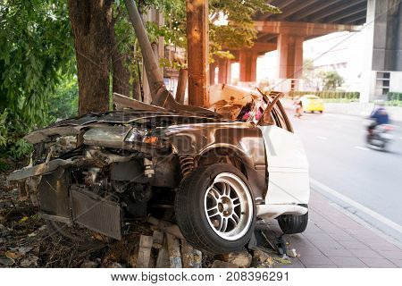 Asia car accident critical car crashes in to tree and electric pole on sidewalk. Car crash in asia with light effect for background.