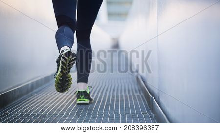 An active fit woman running in an urban environment. Shallow DOF focus on the back shoe.
