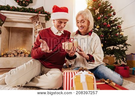 Happy couple. Cheerful blonde keeping smile on her face and bowing head while sitting close to her man