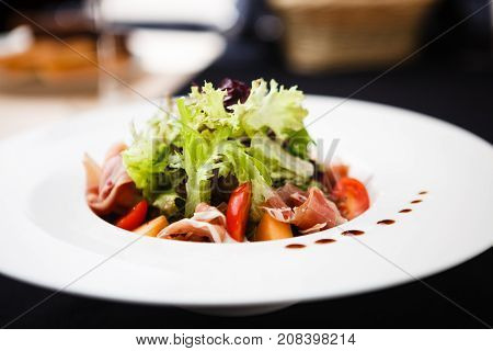 Green salad with Parma ham and melon