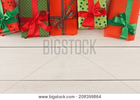 Gift boxes in craft and colorful dotted wrapping paper decorated with satin ribbon bows border on wooden background. Presents for christmas, valentine day or birthday, top view, copy space