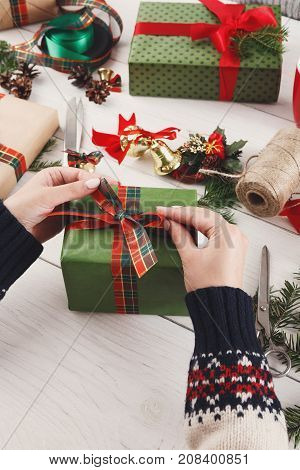 Creative diy hobby. Making bow on modern handmade xmas present, box in stylish paper with satin red ribbon. Woman's hands on white wood table with fir tree branches, decoration of gift.