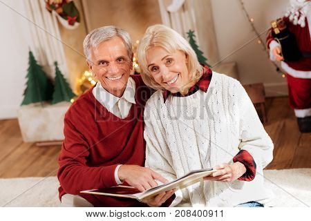 Lets read it. Charming woman keeping smile on her face and bowing head while holding interesting book