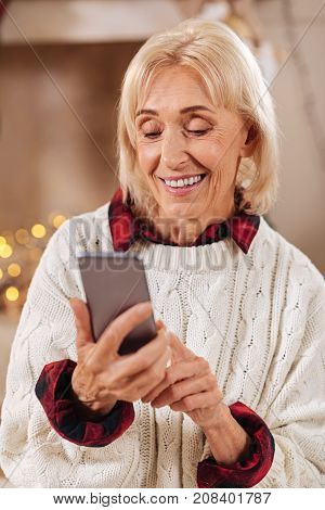 Want to congratulate everybody. Pretty blonde keeping smile on her face and holding telephone in right hand while typing message