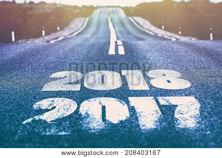 A desert road with the inscription 2017 2018. Concept of the departing old year and new goals.