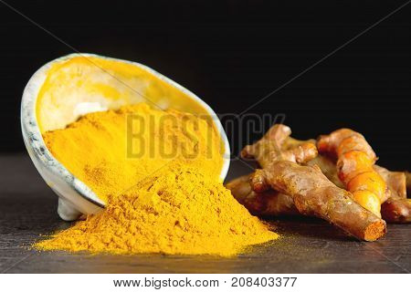 Turmeric Powder And Fresh Turmeric. Dark Background. Space For T