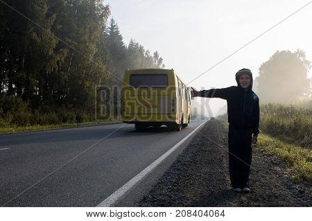 A boy in a dark hooded sweatshirt hitchhiking on a forest road in a fog