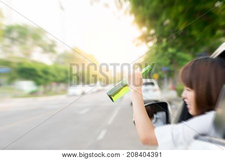 Drunk woman driving and holding beer bottle outside a car