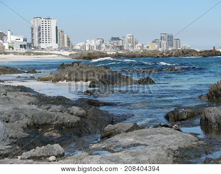 BLOUBERG STRAND, CAPE TOWN, SOUTH AFRICA, WITH HUGE BOULDERS IN THE FORE GROUND AND HIGH RISE BUILDINGS IN THE BACK GROUND