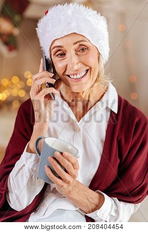 What is up. Amazing woman keeping smile on her face and holding cup in left hand while answering income call