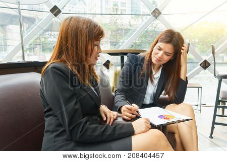 Two business woman talking and thinking about their work - business meeting concept