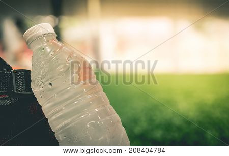 Fresh cool water bottle in soccer field copy space for sport concept
