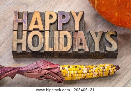 Happy Holidays banner or greeting card in vintage letterpress wood type with pumpkin and corn