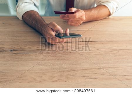 Mobile banking smartphone app used by businessman at office desk. Adult caucasian business person connecting credit card to online internet e-banking service.