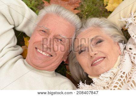 happy Senior couple in autumn park lying