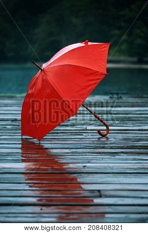 Red umbrella on dock. Forgotten personal accessory on wooden pier on autumn rain.