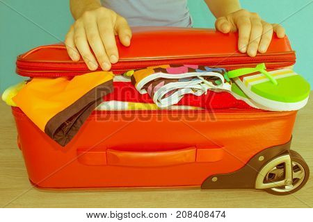 Woman hands packing stuff into suitcase at home. Travel and vacations concept. Suitcase with things for spending summer vacation things prepared for travel - Retro color