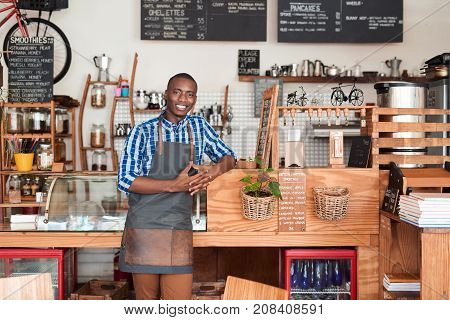 Portrait of a smiling young African entrepreneur wearing an apron leaning against the order counter of his trendy cafe
