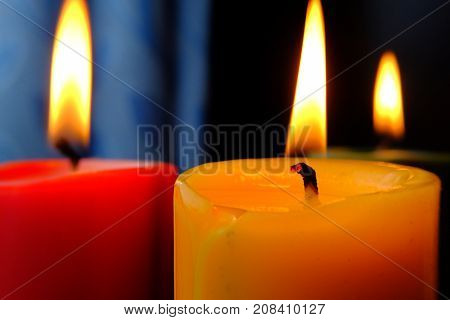 Many candle flames glowing in the dark, create a spiritual atmosphere.
