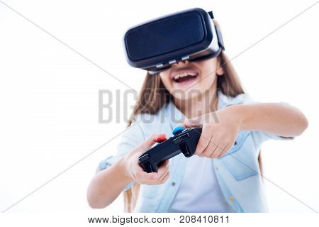 Modern games. Selective focus of a game console while being used by a happy delighted girl for playing video games