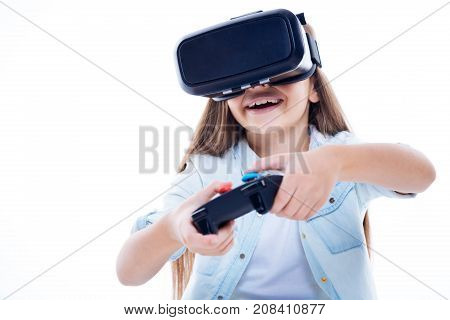 Exiting games. Happy delighted excited girl smiling and playing a video game while using a game console