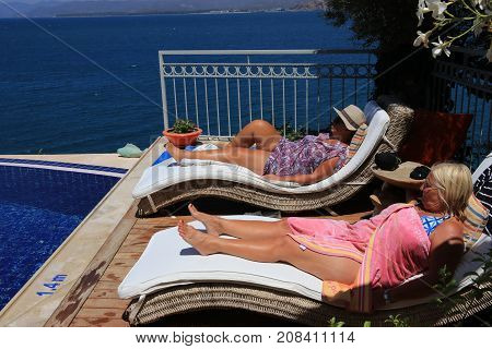 28TH JULY 2017, SOVALYE ISLAND,TURKEY:Two english ladies relaxing on sunbeds next to an infinity pool while on vacation on sovalye island, turkey , 28th july 2017