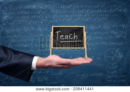 A businessman's hand holds a small easel blackboard with a word Teach on it with equations on the background. Education and tutoring. Math problems. Science and knowledge.