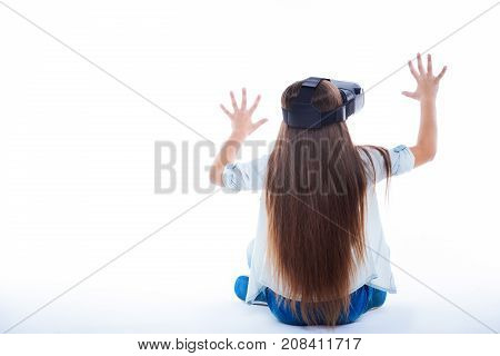 Virtual reality glasses. Positive nice pretty girl sitting on the floor and pressing hands to a virtual screen while experiencing 3d virtual reality