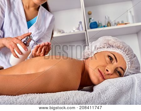 Massage woman therapist making manual therapy back. Hands of masseuse close up. Treatment of spinal injuries 40 old client in spa salon. Beautician uses natural cosmetics. The best spa salon.