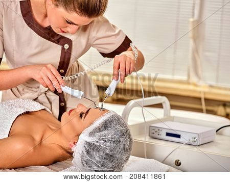 Facial massage at beauty salon. Electric stimulation skin care of woman. Equipment for microcurrent lift face. Anti aging face and neck and close up rejuvenation. The best spa salon.