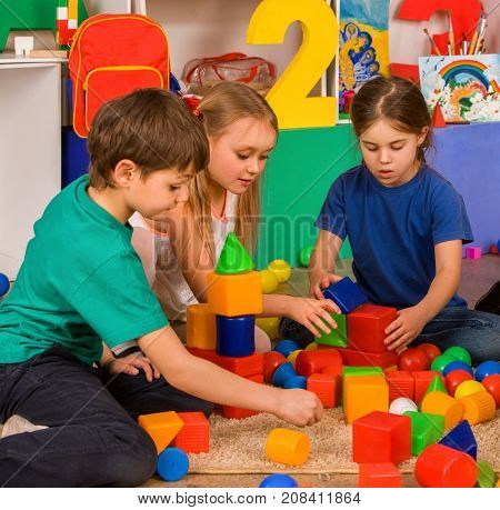Children playing in kids cubes indoor. Lesson in primary school. Body part of girl and boy together play. Kindergarten kids sit on soft carpeton floor. They learn to live in a team.