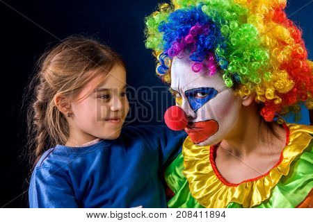 Single parent family. Tired mom after work as clown on birthday on dark background. Adult child relationship. Social problem mad parent. Human hates children.