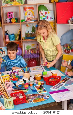 Small students painting in art school class. Children boy and girl drawing by paints on table. Three children are drawing in the kindergarten. They learn to live in a team.