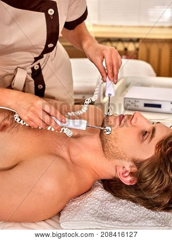 Facial massage at beauty salon. Electric stimulation skin care of man. Equipment for microcurrent lift face. Anti aging face and neck and close up rejuvenation. The best spa salon.