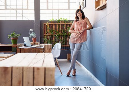 Portrait of a casually dressed young businesswoman smiling confidently while leaning against a wall in a large modern office