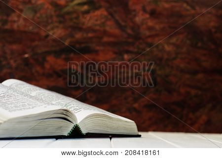 Bible on a white wooden table. Beautiful red wood background. Religion concept