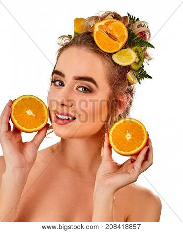 Hair mask from fresh fruits on woman head. Girl with beautiful face and hairstyle hold halves of orange for organic skin and body therapy. Acceleration of hair growth.